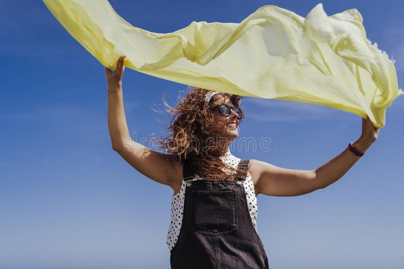 Young caucasian woman outdoors playing with yellow scarf on a windy and sunny day. Lifestyle and summertime stock photography