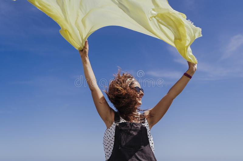 Young caucasian woman outdoors playing with yellow scarf on a windy and sunny day. Lifestyle and summertime stock images
