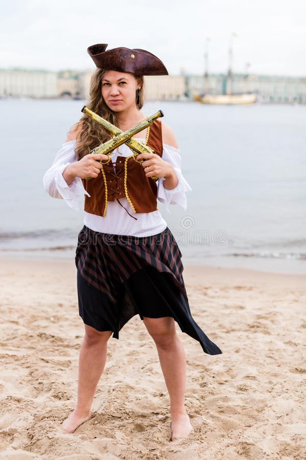 Young Caucasian woman in pirate costume crossed toy guns in front of her. Young Caucasian woman in a black and brown pirate costume crossed toy guns in front of stock photo