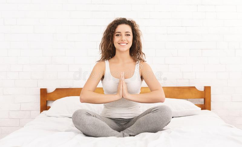 Young caucasian woman practicing yoga in bed stock image