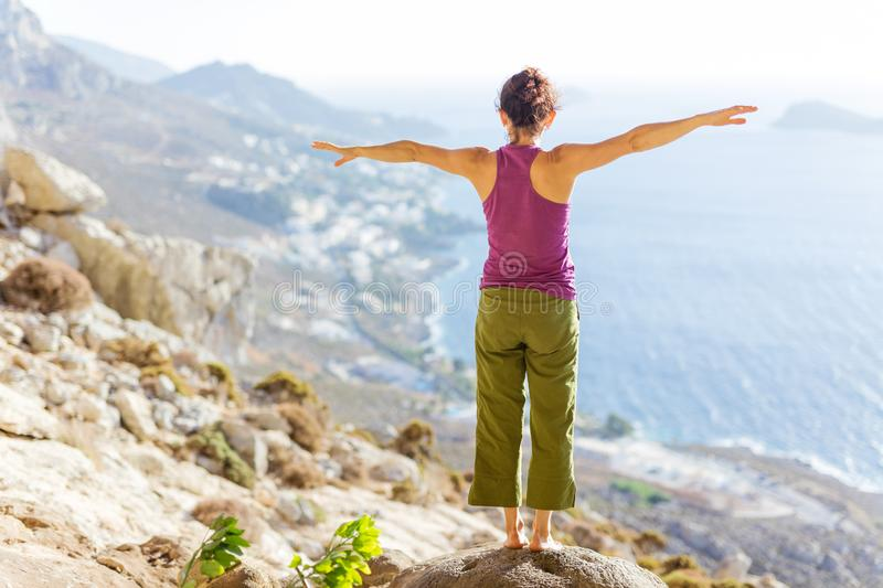 Young Caucasian woman practicing yoga while standing on cliff on sea coast stock photos