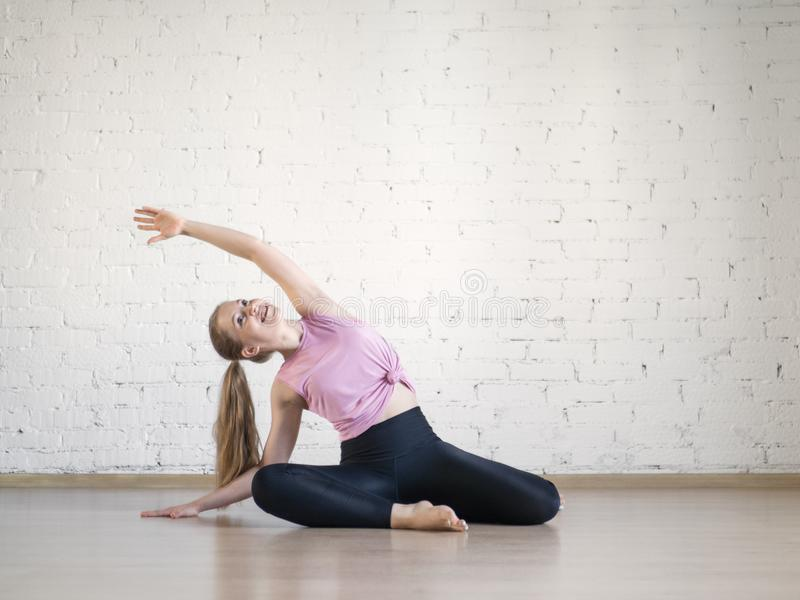 Young caucasian woman practise pilates in fitness studio, mermaid pose, selective focus. stock photo