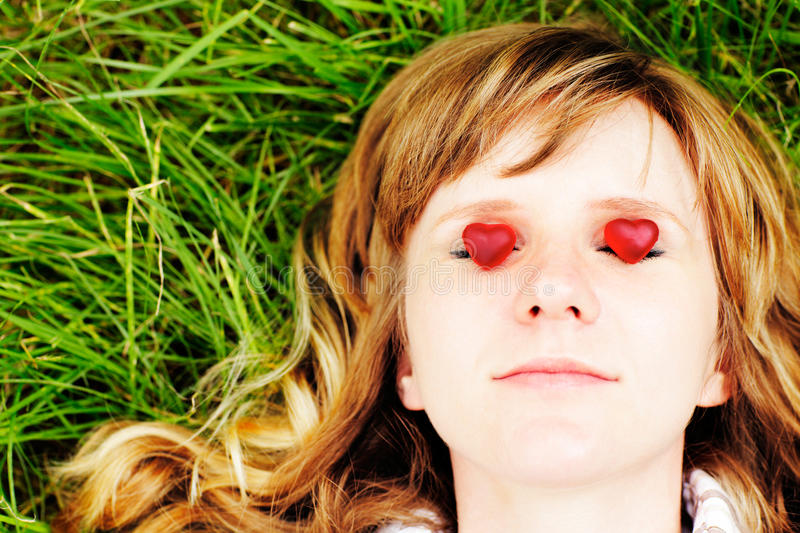 Young caucasian woman with red hair lying down on green grass with eyes closed. There are two small red sweet heart-shaped candies stock image