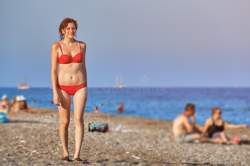 Young caucasian woman in red swimsuit on sea beach royalty free stock photo