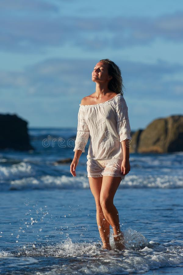 Young caucasian woman refreshing on the beach in summer evening stock images