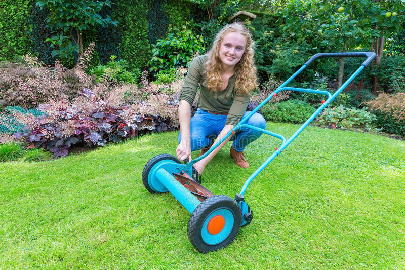 Young caucasian woman reparing lawn mower in garden. European teenage girl fixing lawn mower on green grass royalty free stock image