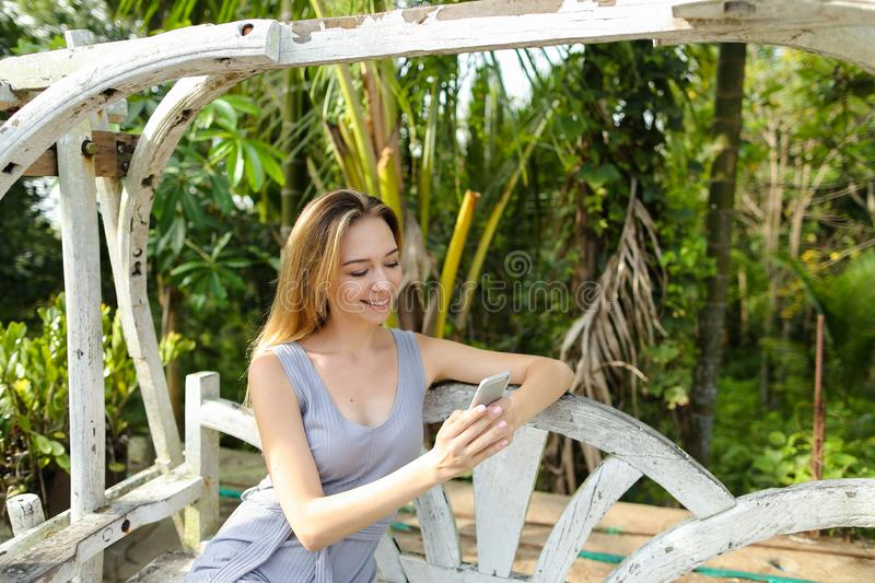 Young caucasian woman riding on swing and using smartphone in exotic garden, palms in background. royalty free stock image