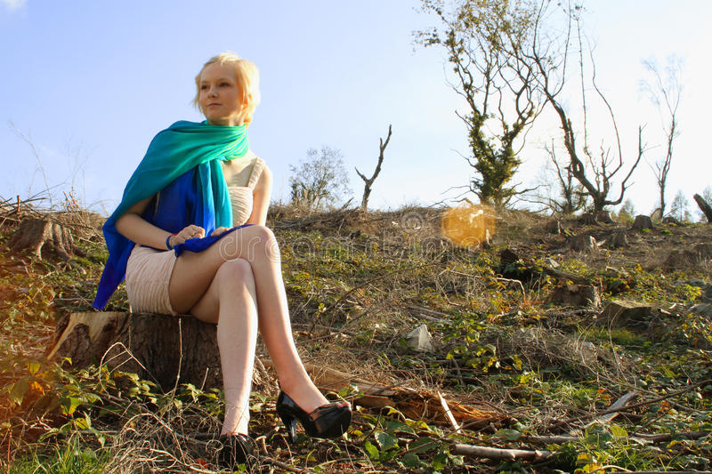 Young caucasian woman seated in barren landscape. Young attractive blonde haired woman in bright scarf sat in a desolate landscape looking pensively into the royalty free stock images