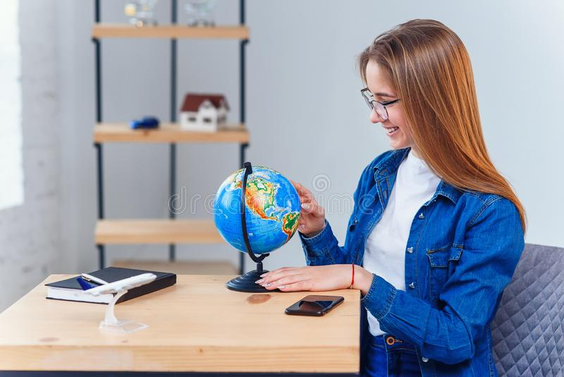 Young caucasian woman sits at the table and rotates the globe to choose the country for vacation and make notes in the. Young caucasian woman sits at the table royalty free stock image