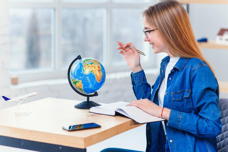 Young caucasian woman sits at the table and rotates the globe to choose the country for vacation and make notes in the. Young caucasian woman sits at the table stock image
