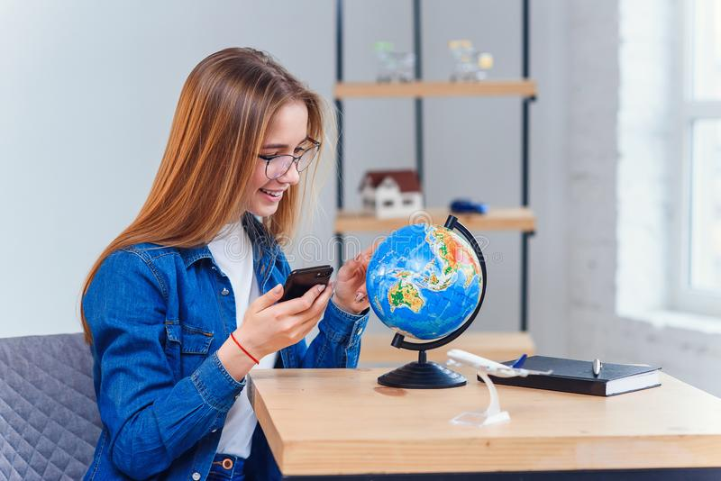 Young caucasian woman sits at the table and rotates the globe to choose the country for vacation and make notes in the. Young caucasian woman sits at the table royalty free stock images