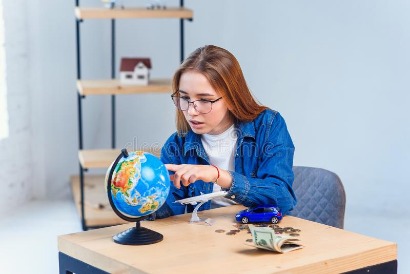 Young caucasian woman sits at the table and rotates the globe to choose the country for vacation and make notes in the. Young caucasian woman sits at the table stock photos