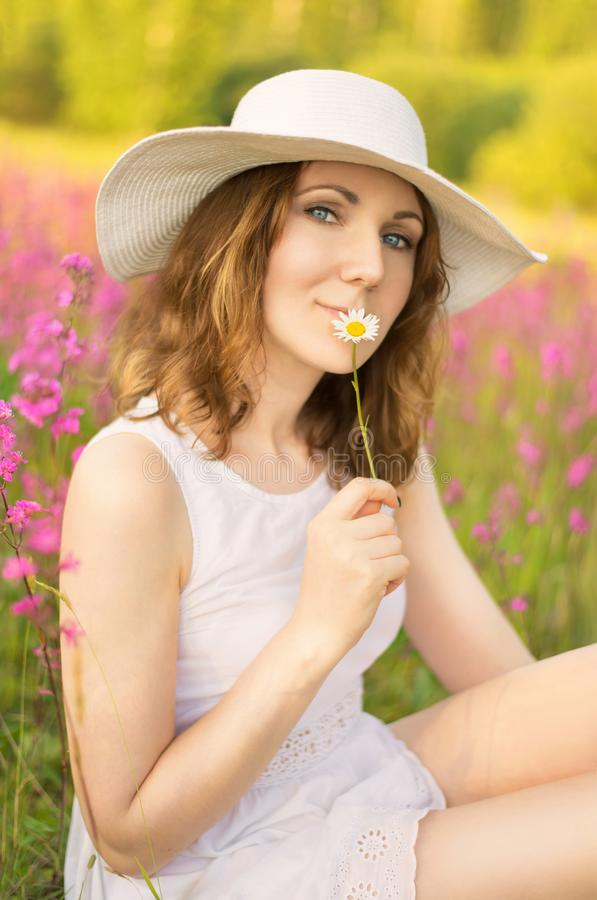 Young caucasian woman sitting on flower field stock photography