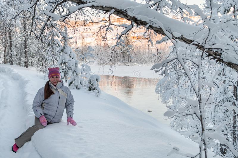 Young Caucasian woman sitting in snow in winter forest, near open water river stock images