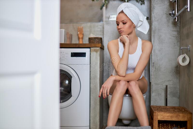 woman sitting on toilet in the bathroom Stock Photo - Alamy
