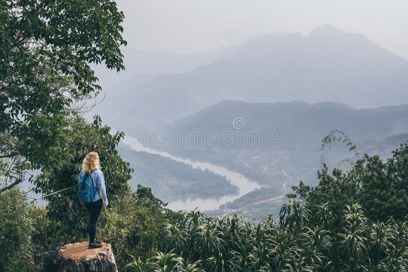 Young Caucasian woman sitting on the top of the mountain overlooking river valley in Nong Khiaw village, Laos. Young Caucasian woman sits on the top of the royalty free stock image