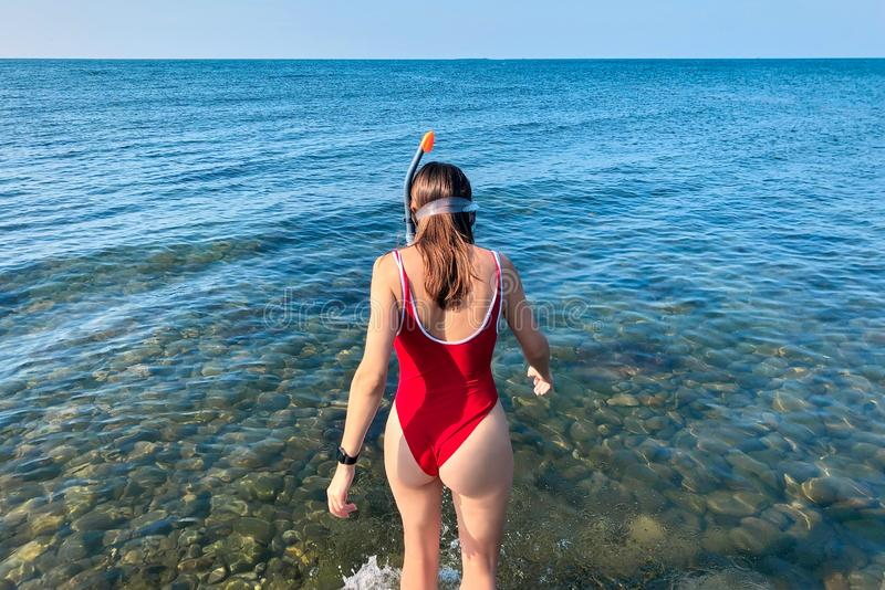 Young caucasian woman in sport red swimsuit goes into the sea with diving mask, back to the camera. Black electronic watch, clean royalty free stock image