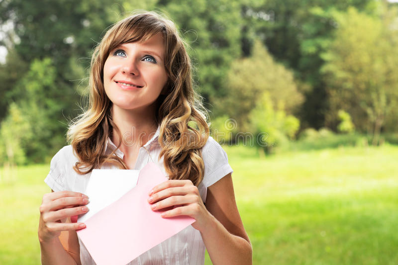 Young caucasian woman standing on blurred green summer background. Holding a blank letter in pink envelope. Letter and envelope co. Uld be used for any custom stock photos