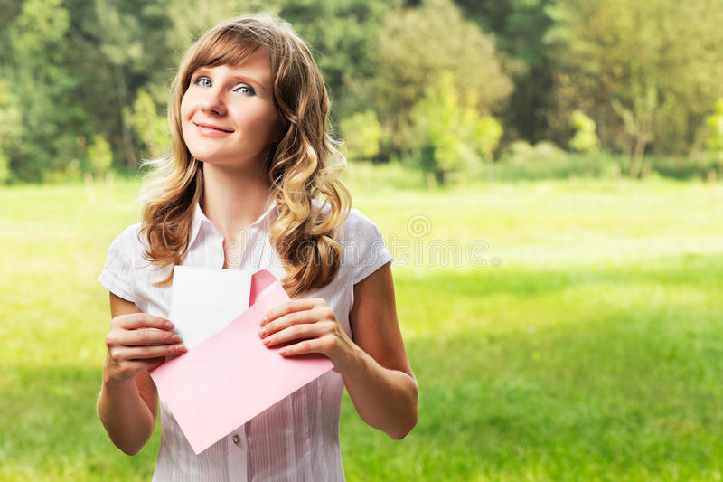 Young caucasian woman standing on blurred green summer background. Holding a blank letter in pink envelope. Letter and envelope co. Uld be used for any custom royalty free stock photo