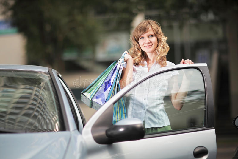Young caucasian woman standing near an open car drivers door with shopping bags. royalty free stock photo