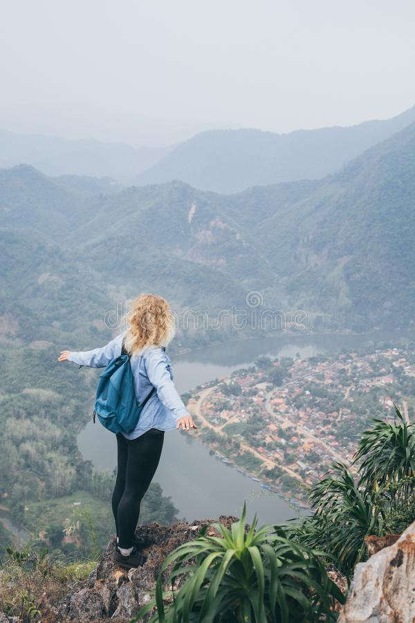 Young Caucasian woman standing on the top of the mountain overlooking river valley in Nong Khiaw village, Laos stock photos