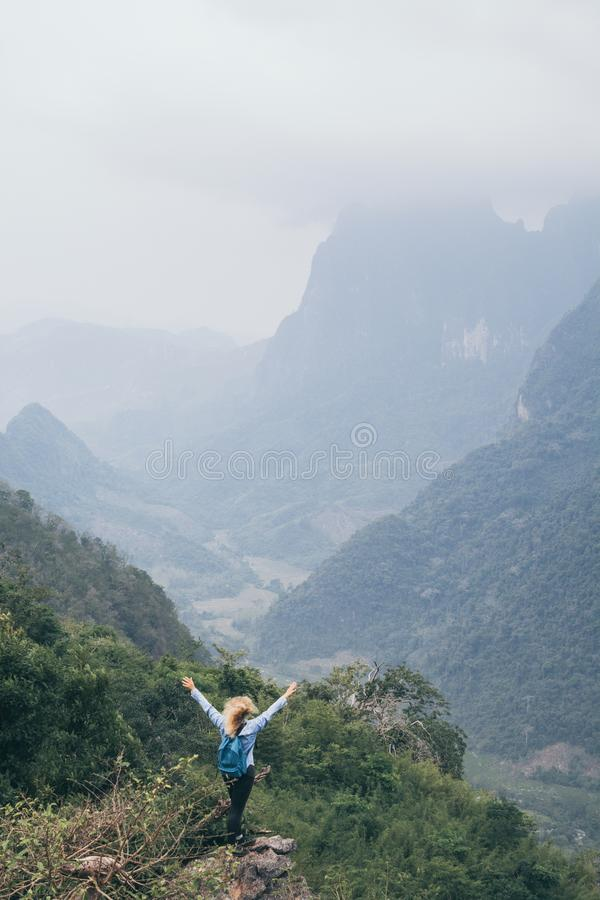 Young Caucasian woman standing on the top of the mountain overlooking river valley in Nong Khiaw village, Laos. Young Caucasian woman stands on the top of the stock photos