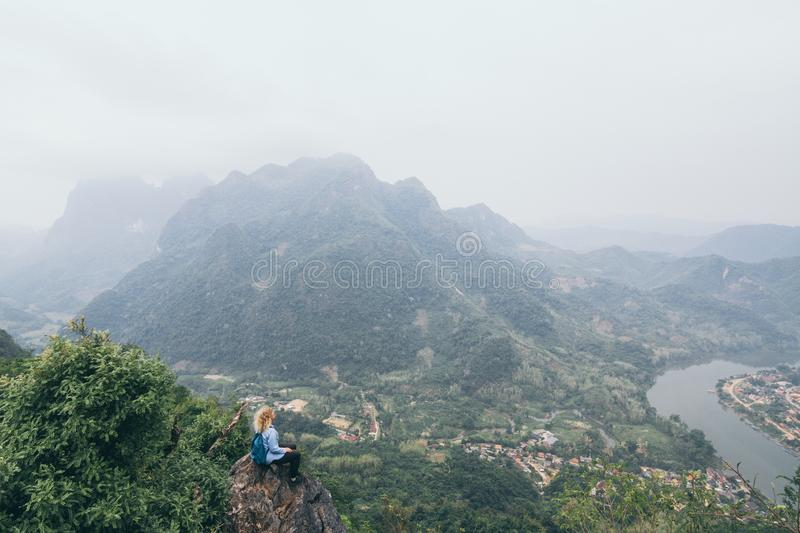 Young Caucasian woman standing on the top of the mountain overlooking river valley in Nong Khiaw village, Laos. Young Caucasian woman stands on the top of the royalty free stock image