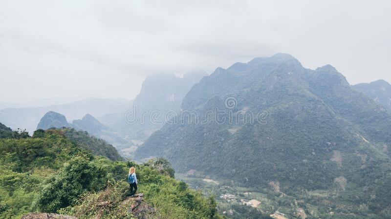 Young Caucasian woman standing on the top of the mountain overlooking river valley in Nong Khiaw village, Laos. Young Caucasian woman stands on the top of the royalty free stock images