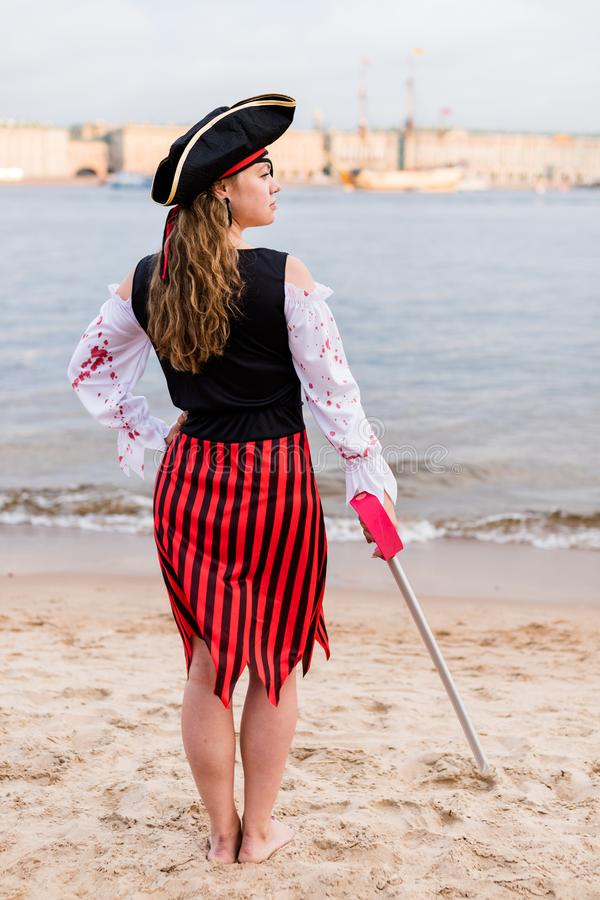 Young Caucasian woman in striped pirate costume lowered toy sword down on beach. Young Caucasian woman in striped pirate costume lowered the toy sword down on royalty free stock images