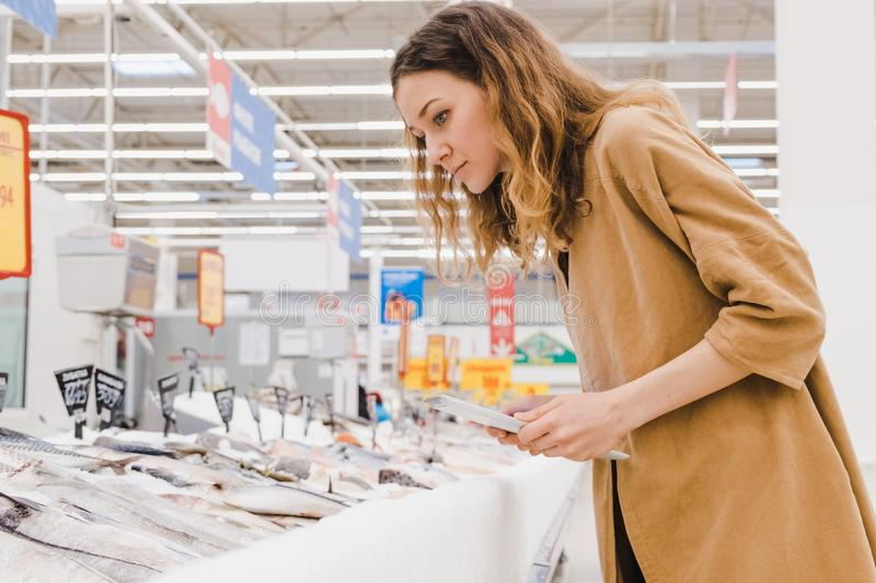 Young caucasian woman with a tablet picks fish in a supermarket royalty free stock photography