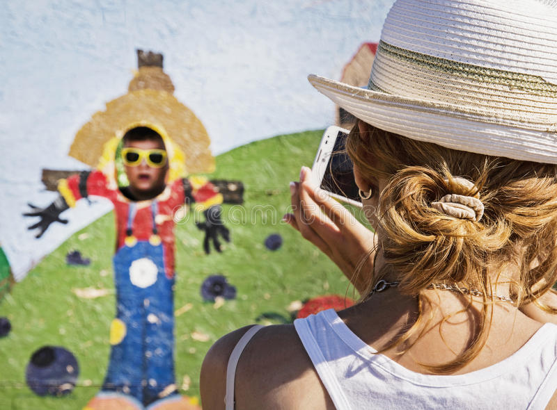 Young caucasian woman takes photo of her son in the family park stock photos