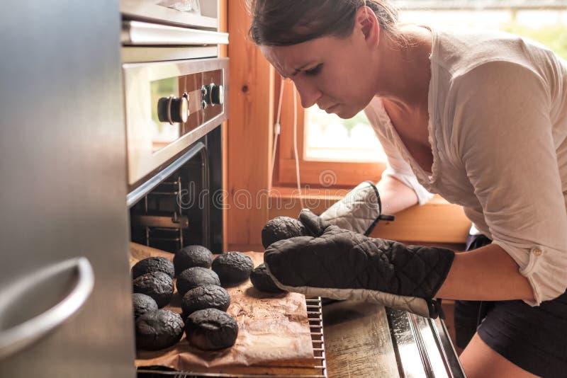 Young caucasian sad woman taking burnt bread stock photos
