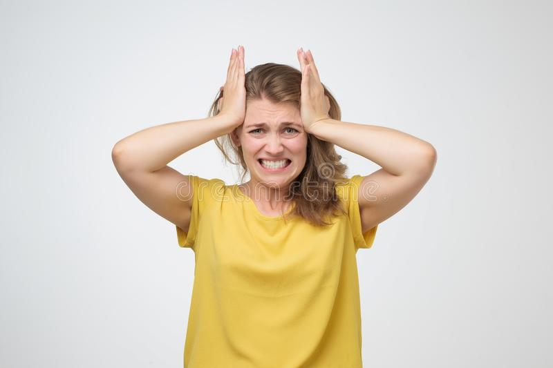 Woman touching her temples feeling stress or terrible headache. Young caucasian woman touching her temples feeling stress or terrible headache. Studio shot stock image