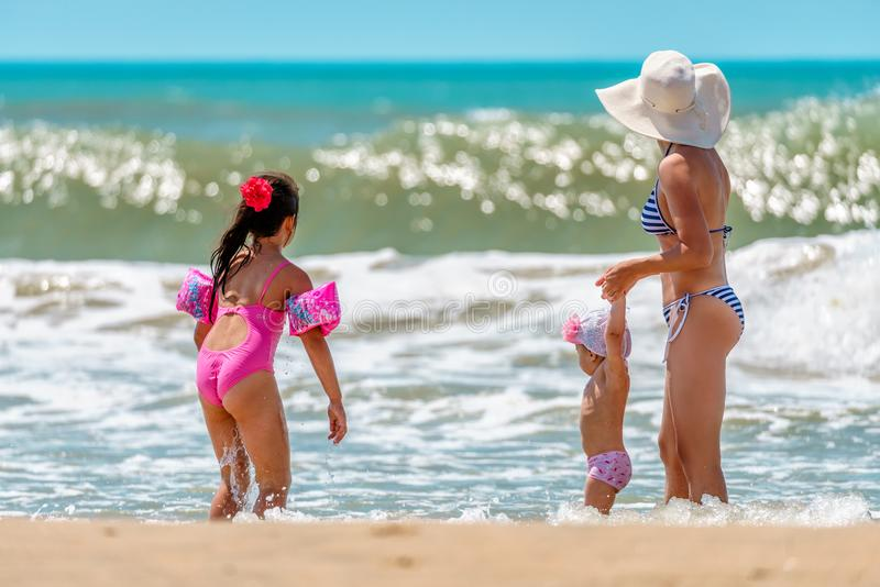 Young Caucasian woman and two small daughters look at coming wave having fun by water on sunny Black Sea beach at storm stock photo