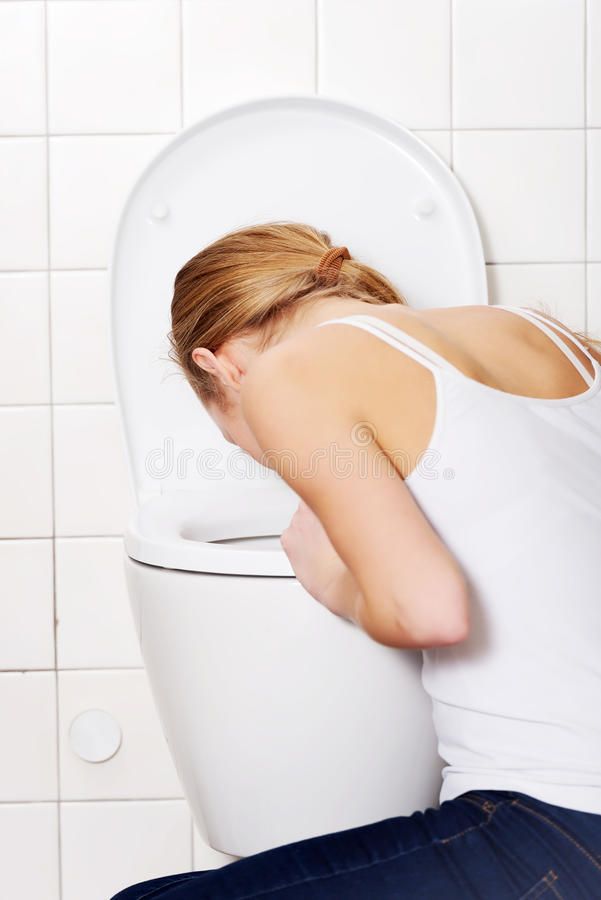 Young caucasian woman is vomiting in the bathroom. Bulimia, sick concept royalty free stock image