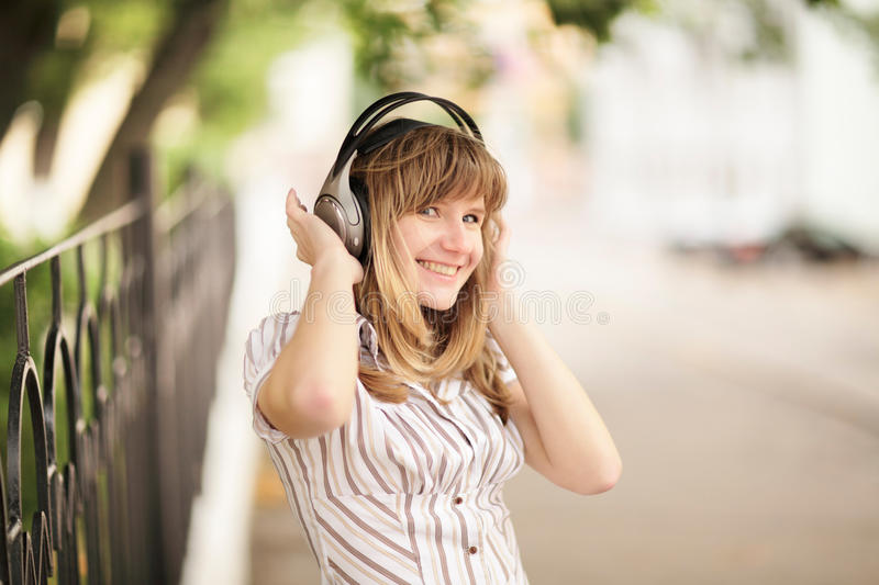 Young caucasian woman walking on the street and listening to the music using big headphones. stock image