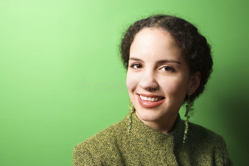 Young Caucasian woman wearing green clothing. Smiling young Caucasian woman on green background wearing green clothing royalty free stock image