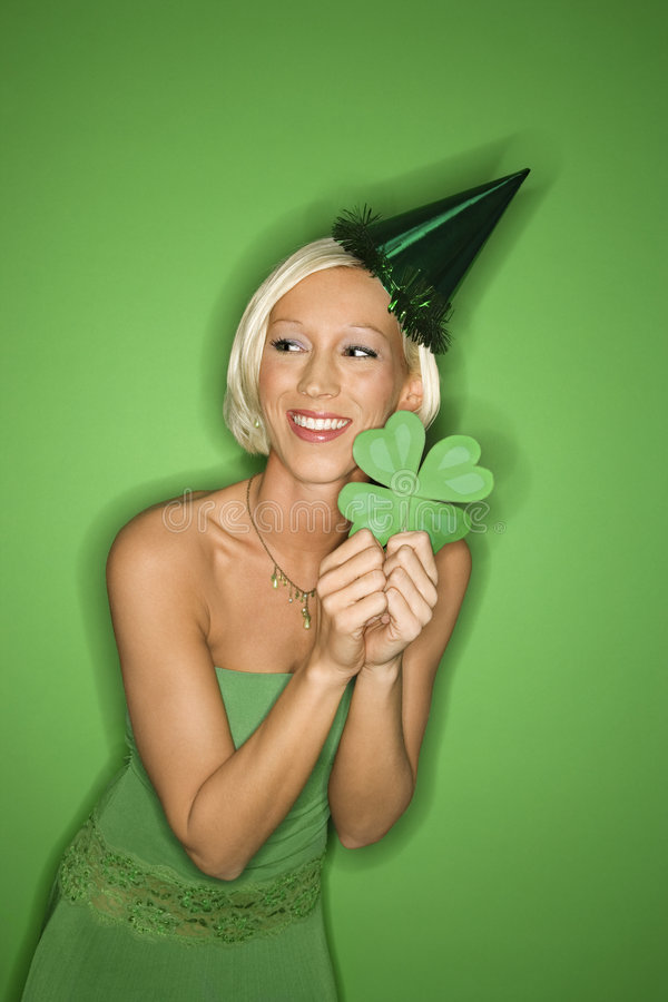 Download Young Caucasian Woman Wearing Party Hat And Holding Shamrock. Stock Image - Image of indoors, female: 2043935