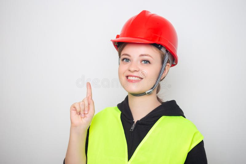 Young caucasian woman wearing red safety hard hat and reflective vest, smiling stock photos
