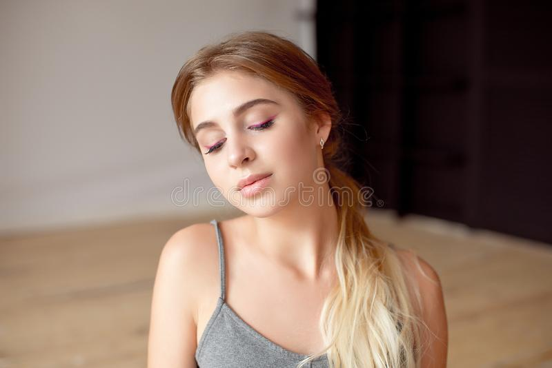 Young caucasian woman wearing in sports bra over background smiling with hands on hips with closed eyes and. Close-up young caucasian woman wearing in sports bra royalty free stock photo