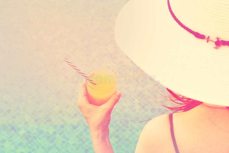 Young caucasian woman in white beach hat swimsuit holds glass of freshly pressed tropical fruits orange juice sitting by pool stock photo