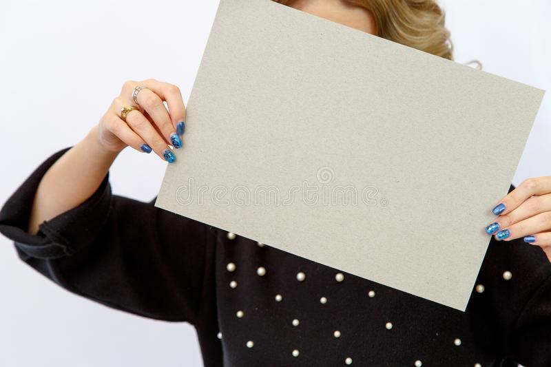 Young Caucasian woman on a white isolated background holding a sheet of cardboard without labels. Young Caucasian woman on a white isolated background holding a stock image