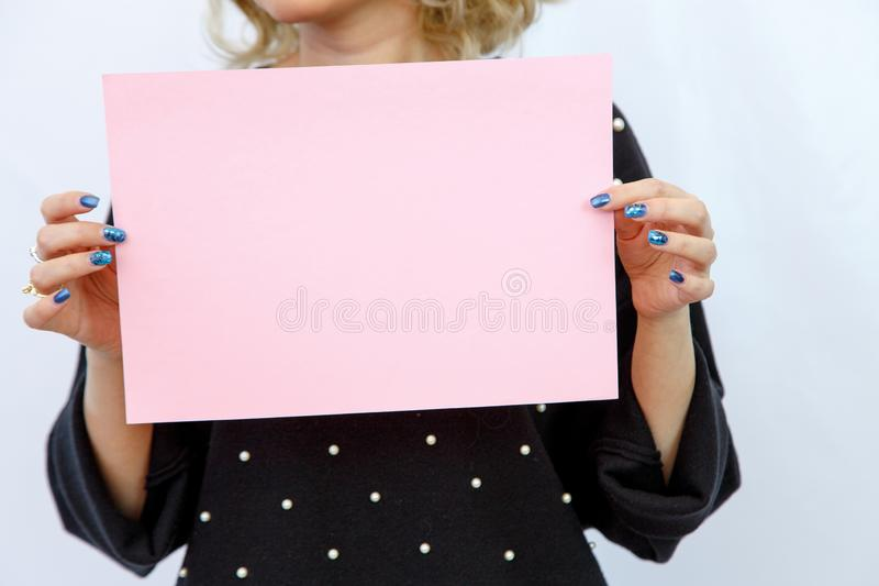 Young Caucasian woman on a white isolated background holding a sheet of cardboard without labels. Young Caucasian woman on a white isolated background holding a royalty free stock image