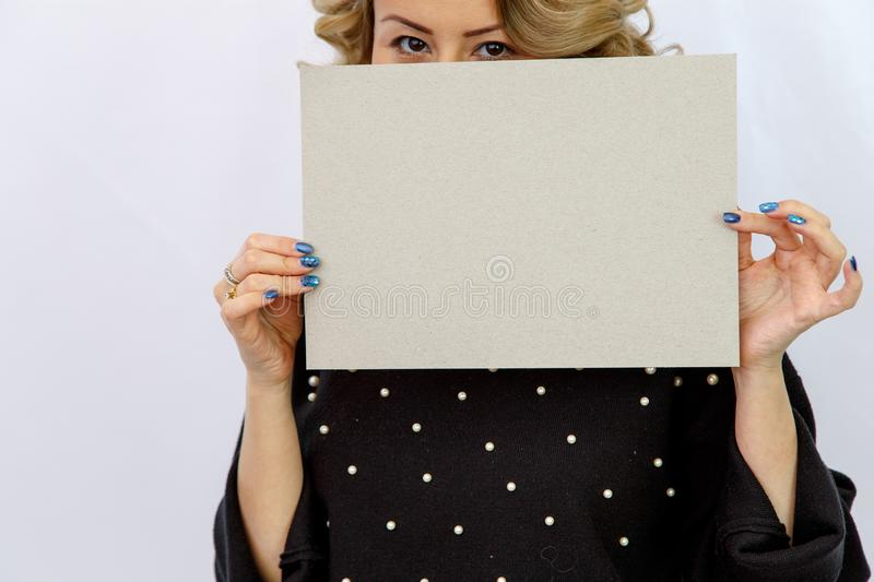 Young Caucasian woman on a white isolated background holding a sheet of cardboard without labels. Young Caucasian woman on a white isolated background holding a royalty free stock photography
