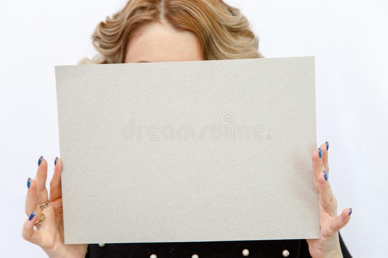 Young Caucasian woman on a white isolated background holding a sheet of cardboard without labels. Young Caucasian woman on a white isolated background holding a stock photo