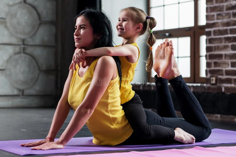Young Caucasian woman doing stretching exercise for spine together with a child sitting on her back in gym royalty free stock images