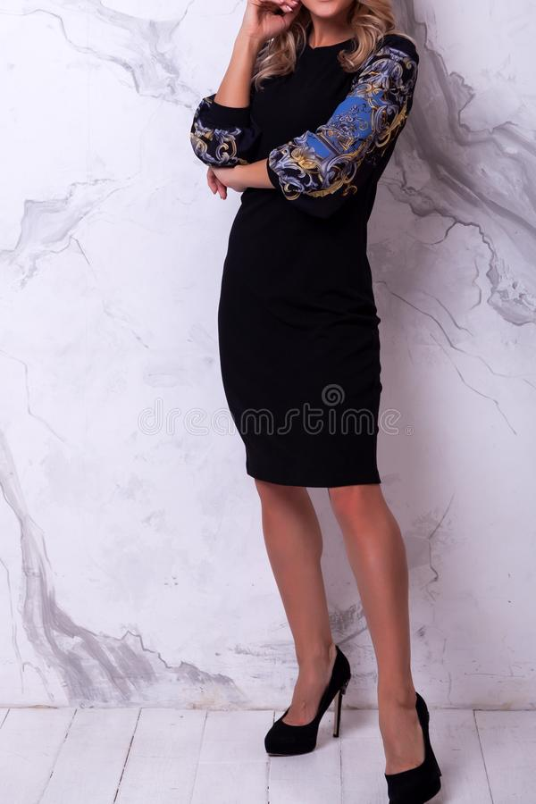 New Year`s fashion trends. Young celebrating woman in black dress . Beautiful model portrait isolated over studio background white wall.Happy woman celebrate stock photos