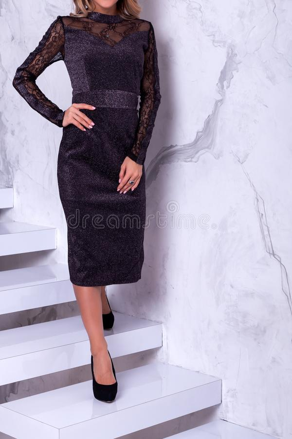 New Year`s fashion trends. Young celebrating woman in black shiny dress . Beautiful model portrait isolated over studio background white wall.Happy woman royalty free stock photography