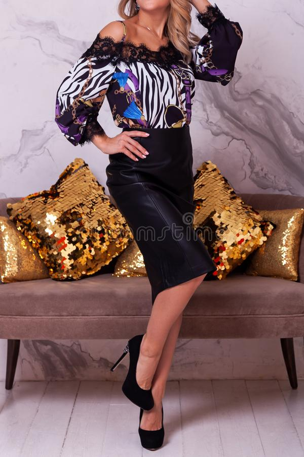 New Year`s fashion trends. Young celebrating woman in shiny blouse and black skirt . Beautiful model portrait isolated over studio in the background there is a stock photo