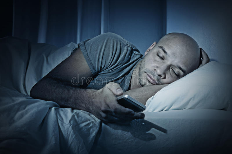 Young cell phone addict man sleeping at night in bed while using smartphone royalty free stock photography
